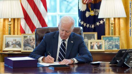 Biden signs the American Rescue Plan on March 11, 2021.
