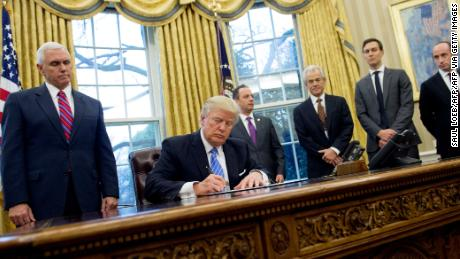 Former President Donald Trump signing an executive order alongside White House officials on January 23, 2017. Among three orders signed was one reinstating and expanding the Mexico City Policy.